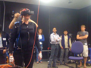 A boot camp scene from TDLC's Motion Capture/Brain Dynamics Facility, located in the San Diego Supercomputer Center.(L-R) Natasha Avis, UC Santa Barbara (in the body suit); David Peterson, Institute for Neural Computation postdoc adjusting the head mounted display; Mary Mullane, UCSD Psychology department; Ashish Tawari, UCSD Electrical and Computer Engineering department; Cuong Tran UCSD Computer Science and Engineering department; and Cory Rieth UCSD Psychology department.