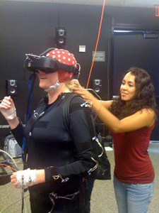 A camp scene from TDLC's Motion Capture/Brain Dynamics Facility, in the San Diego Supercomputer Center.(L-R) Natasha Avis, UC Santa Barbara (in the body suit); and Angelica Rodriguez, a post-baccalaureate researcher in UC San Diego's Machine Perception Lab, which is housed at Calit2.
