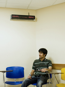 A student sits underneath an installed LED digital sign