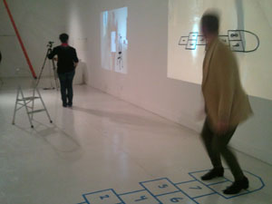 A participant in the 'Becoming Wendy' performance plays hopscotch while looking at a digital projection of the playing field.