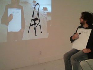 Michael Trigilio, who participated in the performance, draws a self-portrait while looking at a projected image of himself.