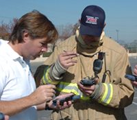 Calit2 researcher coaches firefighter on new PDA application for emergency response.