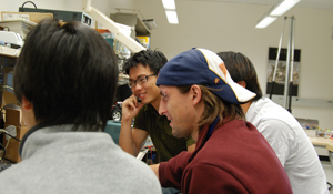 Javier Rodriguez Molina (center, in hat) advises students on their Engineering Group Design Project.