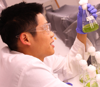 Garfield Kwan inspects a beaker full of algae