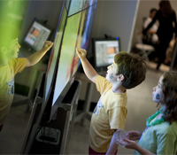 Children interact with the OptIPortable at the Knowledge Exchange Corridors exhibition at the galler