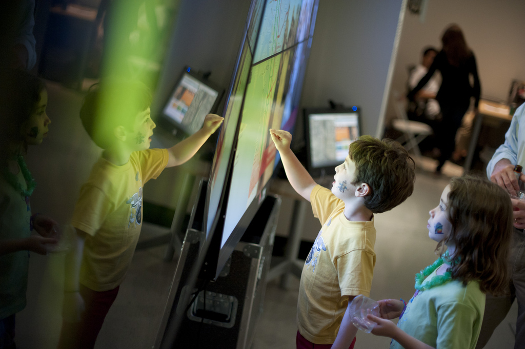 Children interact with the OptIPortable at the Knowledge Exchange Corridors exhibition at the gallery@calit2.