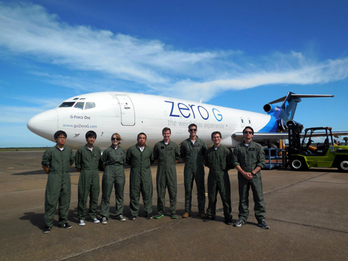 The UC San Diego Microgravity team poses in front of the special NASA plane they used for their experiments on biofuels in space.