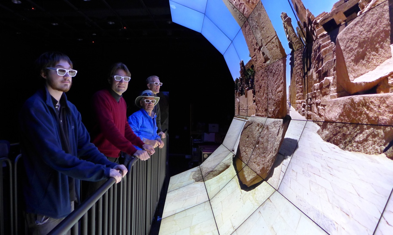 QI Researchers examining images from the Exodus exhibition on the WAVE