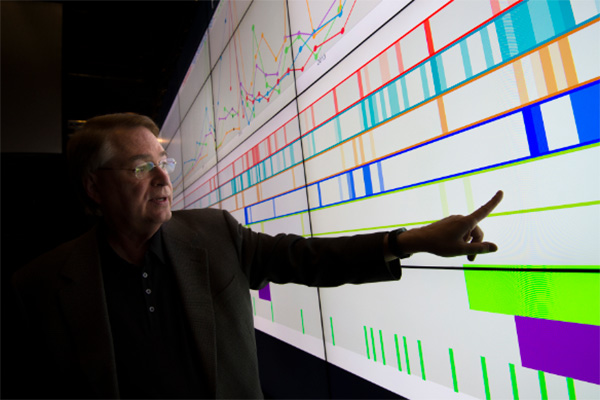 Larry Smarr points to health data on the Vroom visualization wall in the Qualcomm Institute.