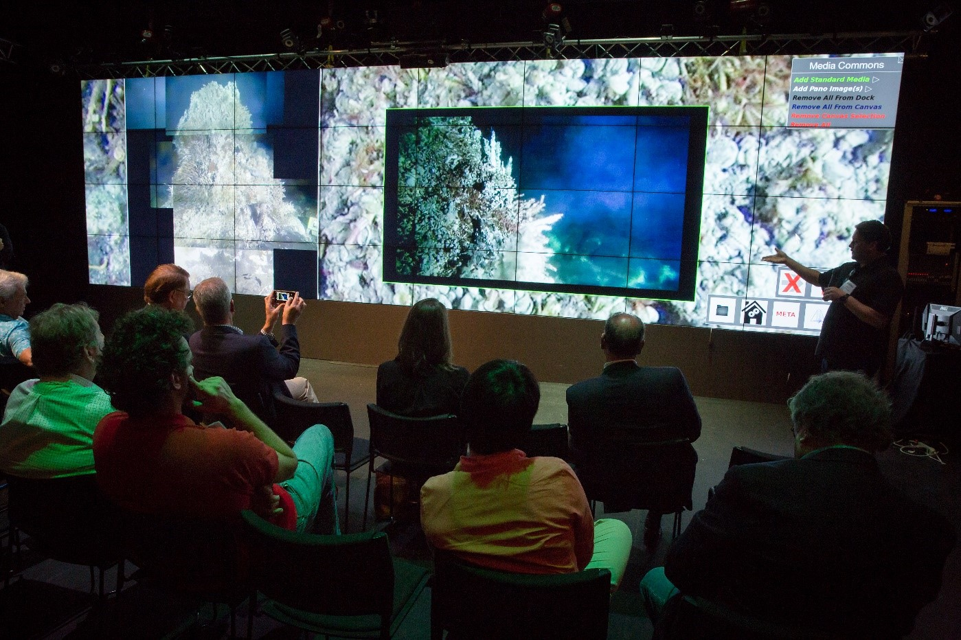 Figure 2. The large Video Wall in the Qualcomm Institute V-Room hosts several high-resolution images of the Mushroom structure, and a live feed of HD Video directly from the seafloor as an inset.  Audience members can be seen in the foreground, giving a sense of the size of the display (10 feet high x 36 feet long).