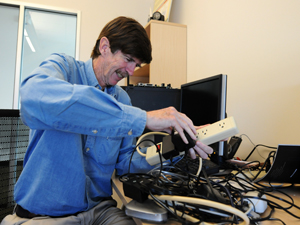 "Calit2 researcher Doug Palmer is frustrated by the many external ""wall warts"" he has to use to power his devices."