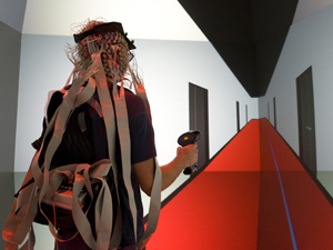 "Ed Kezeli, a recent Computer Science and Engineering alumnus of UCSD, serves as a test subject in the ""way-finding"" study. Here, Kezeli is navigating through a 3-D rendering of a corridor in Calit2's Atkinson Hall, designed to be totally ambiguous and provide few orientation cues."