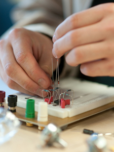 Hands building a guitar pedal with circuits
